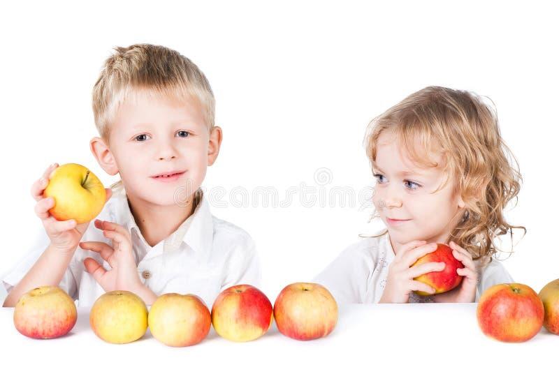 Deux gosses avec des pommes d'isolement sur le blanc photo stock