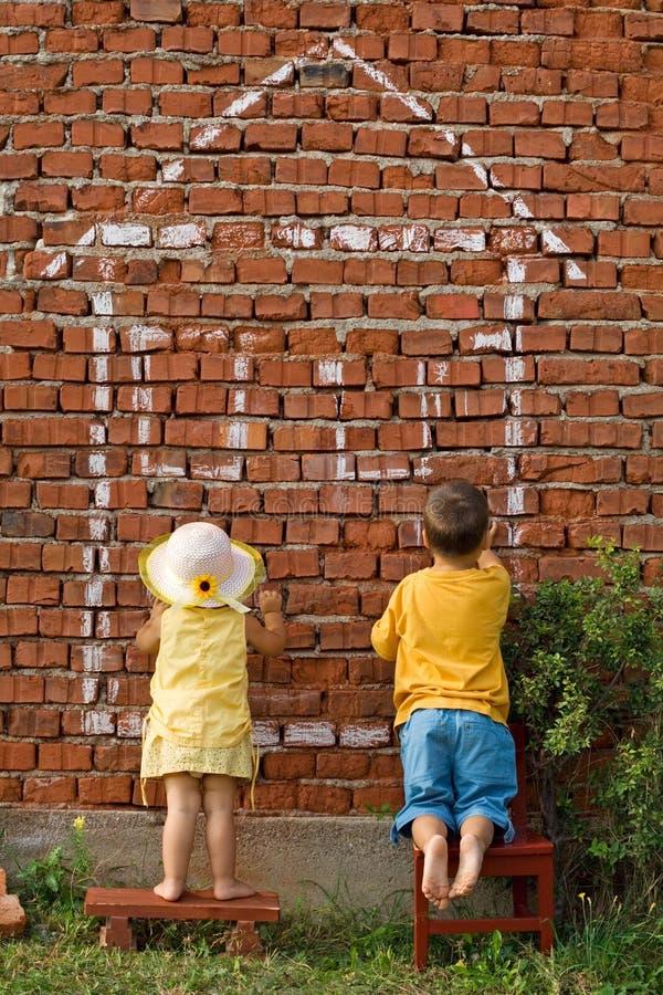 Deux gosses dessinant une maison photographie stock libre de droits