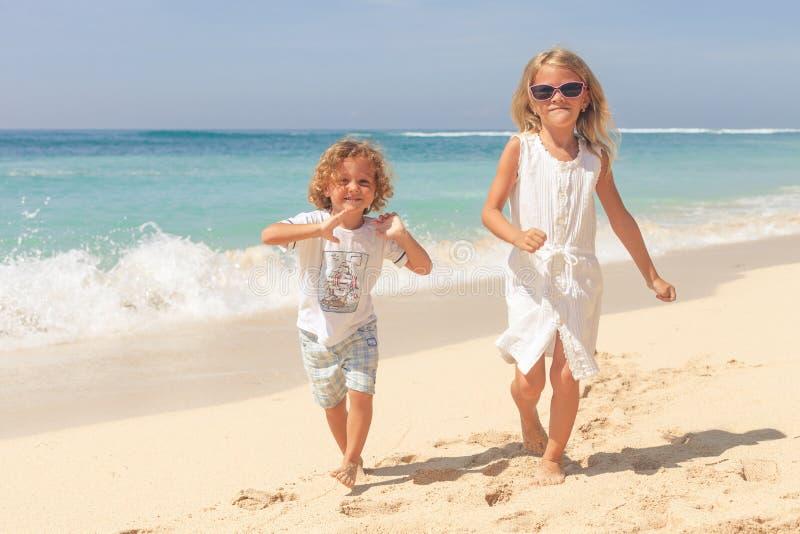 Deux gosses heureux jouant sur la plage photo libre de droits