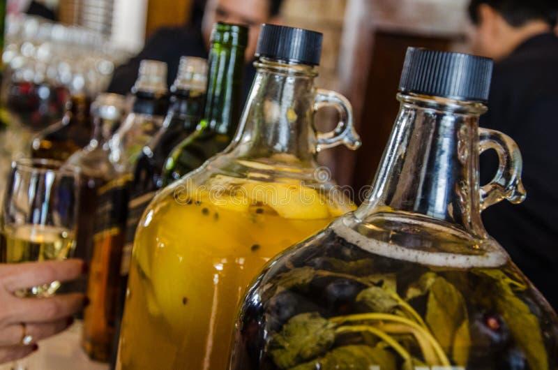 Deux grandes bouteilles en verre de pisco avec le fruit macéré photographie stock libre de droits