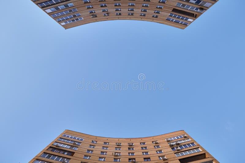 Deux grandes maisons incurvées s'élèvent contre le ciel bleu photos libres de droits