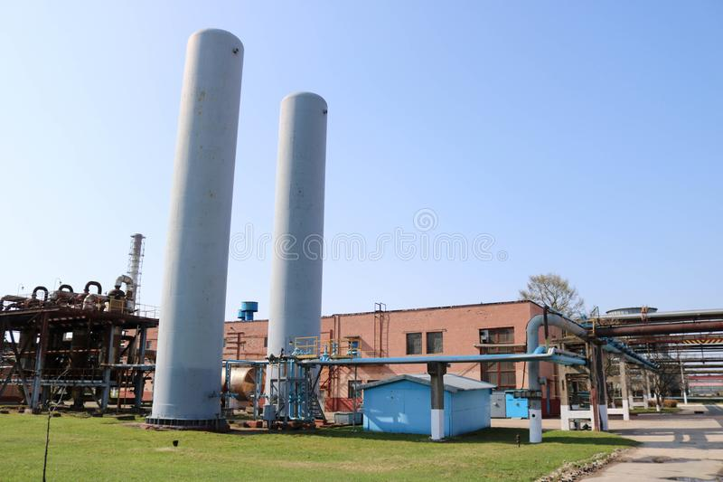 Deux grands réservoirs de bleu pour stocker l'air, l'azote et un bâtiment de production à un raffinerie de pétrole, produit pétro photos libres de droits