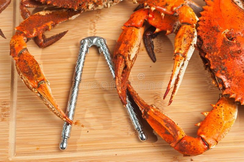 Deux griffes bleues colossales de chesapeake cuit et chevronné à la vapeur marchent en crabe sur une planche à découper en bois photos stock