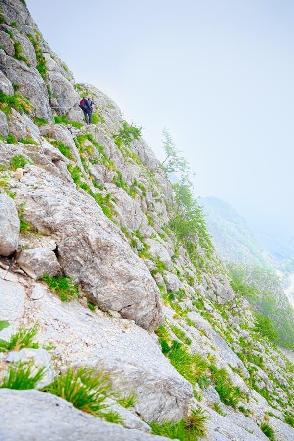 Deux grimpeurs montent un chemin découpé dans la roche pure photographie stock