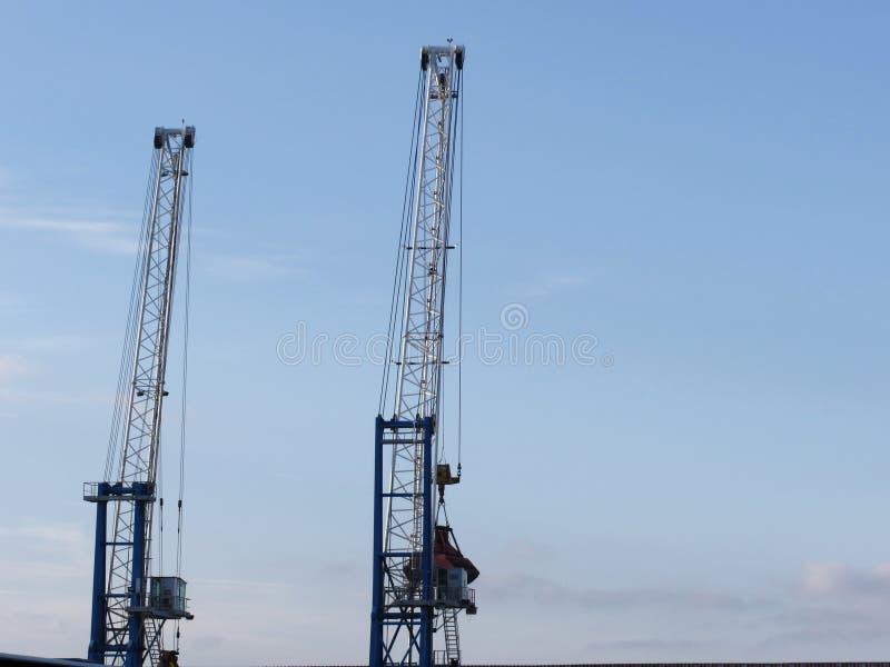 Deux grues de port maritime pour soulever des marchandises outre des plate-formes avec le fond de ciel bleu photos libres de droits