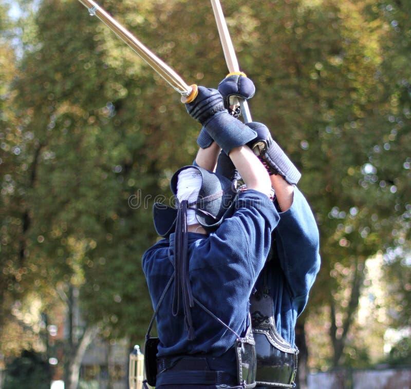 Deux guerriers courageux du combat de kendo combattent avec les épées en bambou photo libre de droits