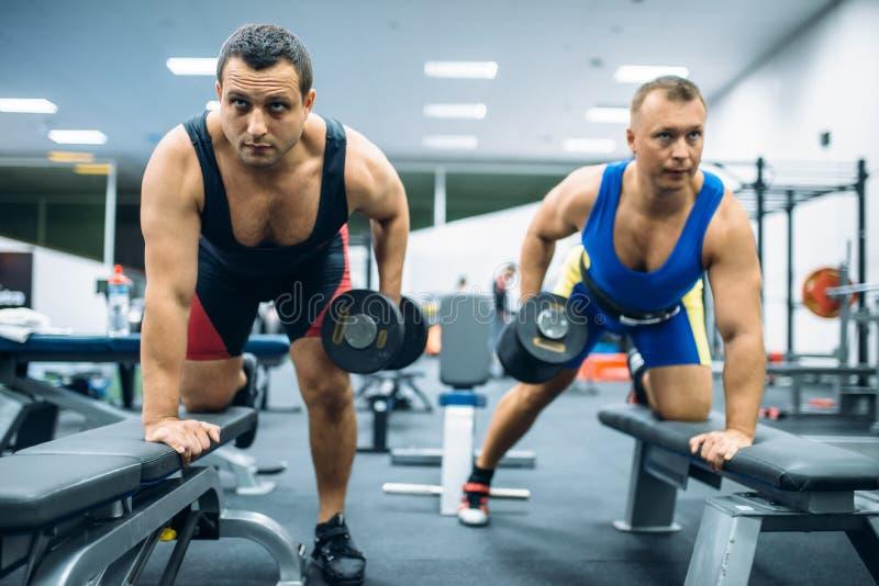 Deux halt?rophiles faisant l'exercice avec des halt?res photographie stock