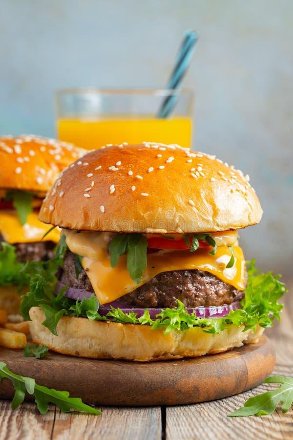 Deux hamburgers faits maison frais avec les pommes de terre et le jus d'orange frits sur une table en bois photos stock