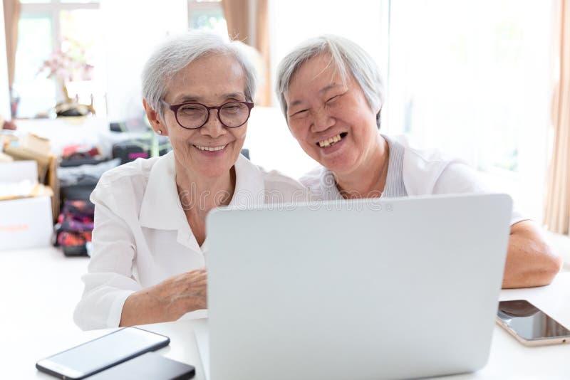 Deux heureux femme, soeurs ou amis asiatiques sup?rieurs parlant et appr?ciant ? l'aide de l'ordinateur portable ensemble ? la ma images stock