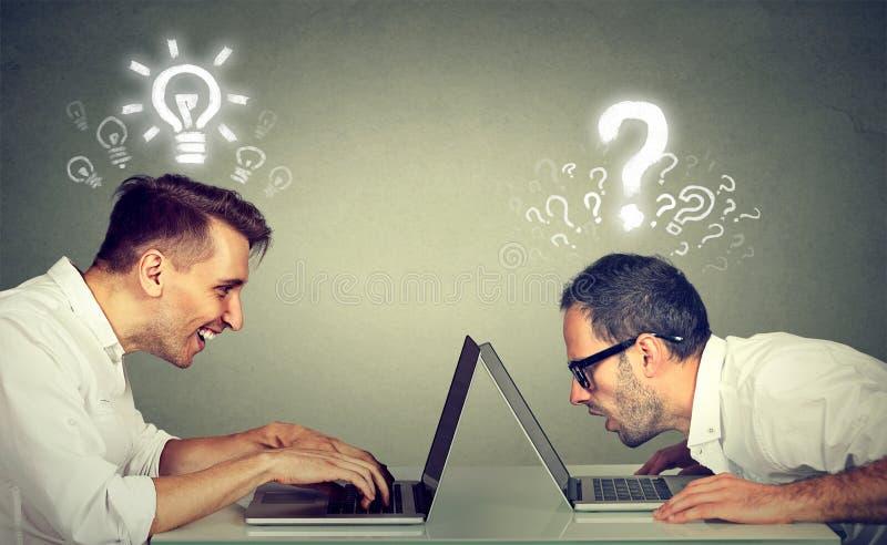 Deux hommes à l'aide de l'ordinateur portable un instruit a des idées lumineuses que l'autre ignorant a des questions photo libre de droits