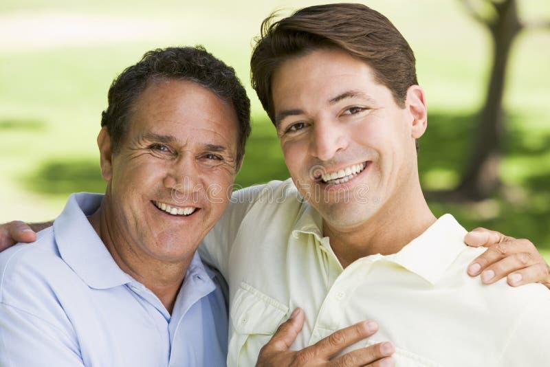 Deux hommes à l'extérieur embrassant et souriant images stock