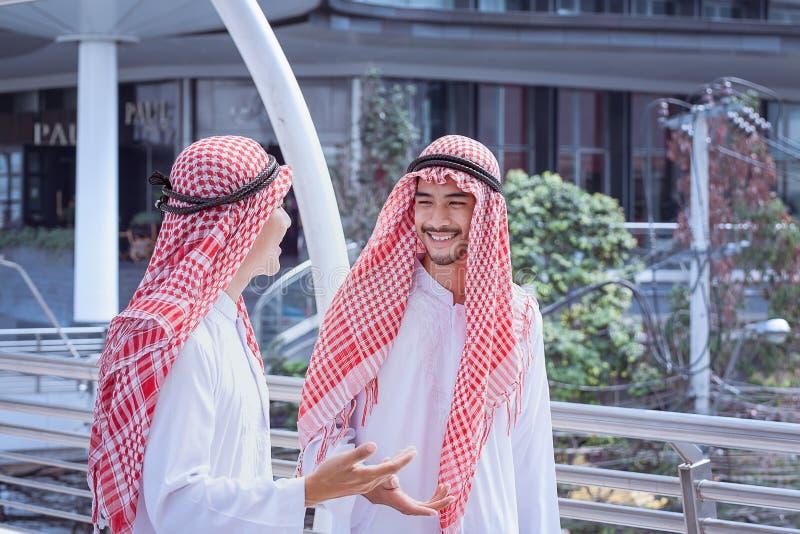 Deux hommes Arabes d'affaires discutent et marchent ensemble autour de moderne photographie stock libre de droits
