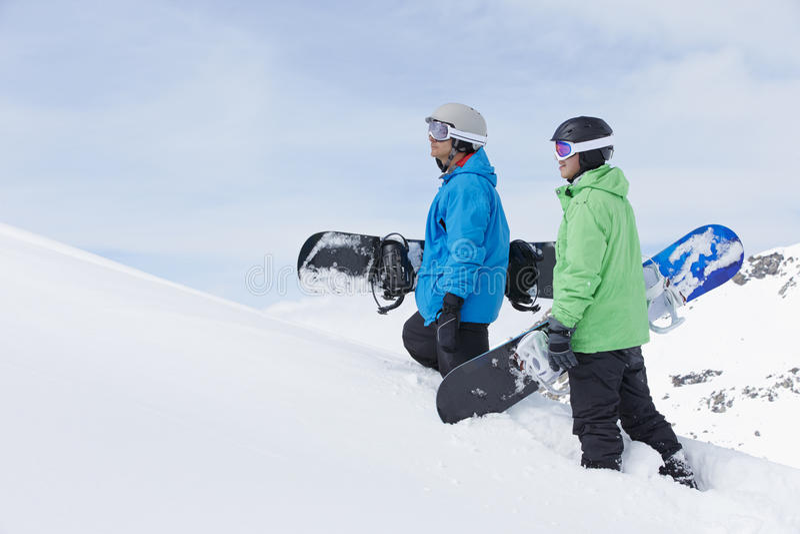 Deux hommes avec des surfs des neiges sur Ski Holiday In Mountains photographie stock