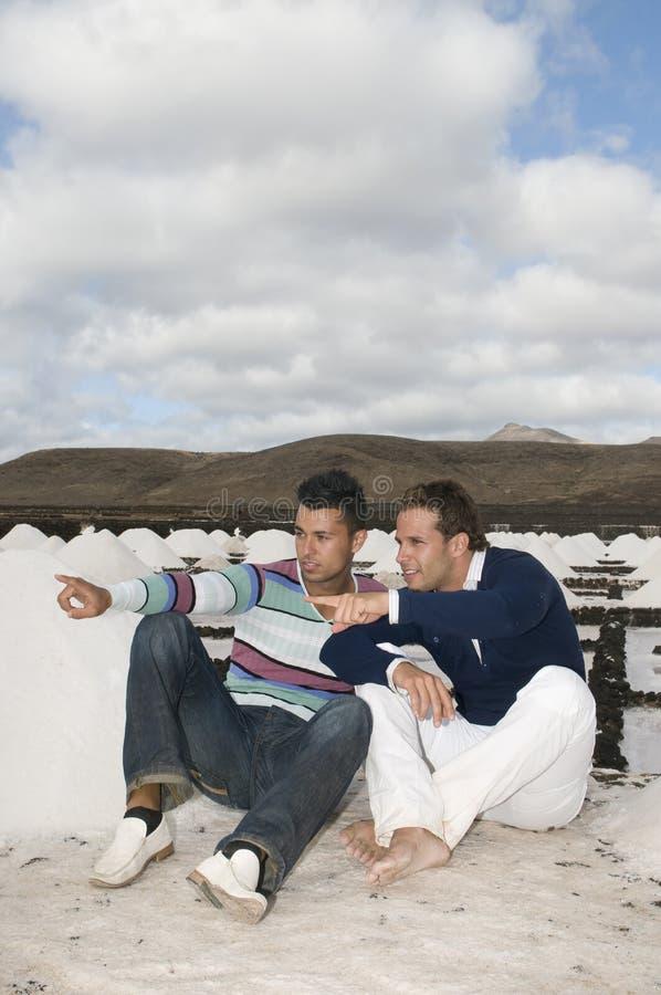 Deux hommes ayant l'amusement entre les montagnes de sel photos stock