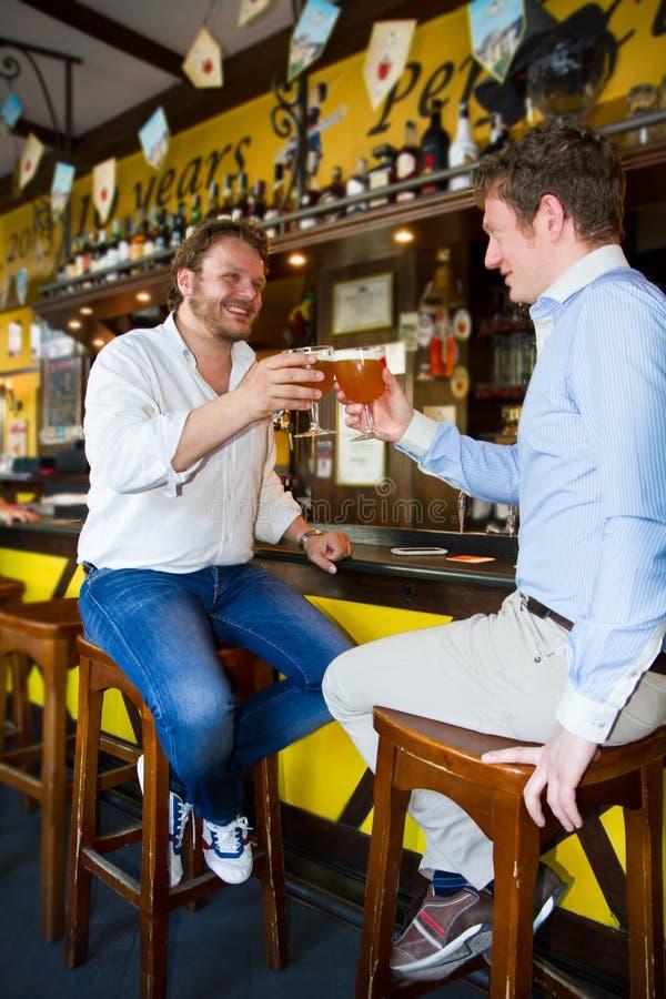 Deux hommes buvant de la bière dans le bar image stock