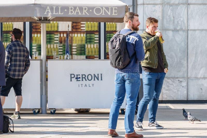 Deux hommes buvant de la bière en dehors d'une barre à Canary Wharf sur un d ensoleillé images libres de droits