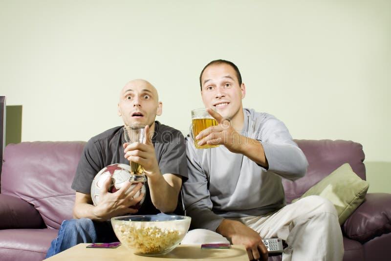 Deux hommes buvant de la bière et observant le football à la TV image libre de droits