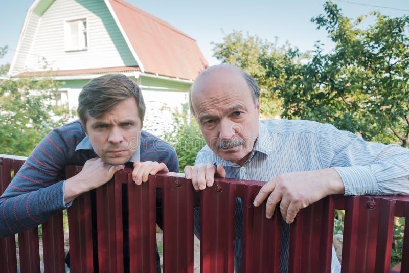 Deux hommes caucasiens observant soigneusement au-dessus de la barrière photos libres de droits