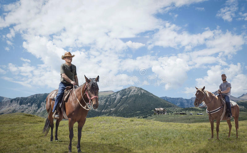 Deux hommes chaque séance sur un cheval avec les montagnes majestueuses à l'arrière-plan photo libre de droits