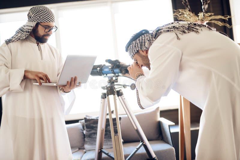 Deux hommes d'affaires arabes avec l'ordinateur portable et le télescope à la chambre d'hôtel photo stock