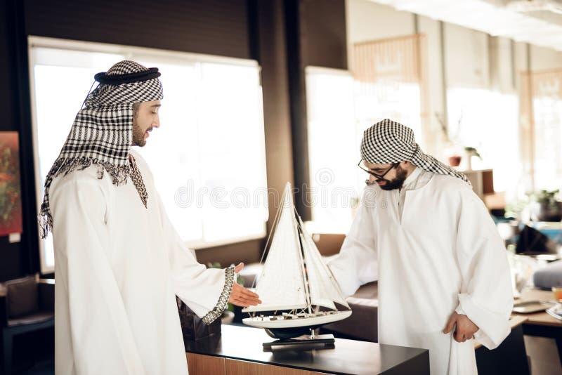 Deux hommes d'affaires arabes avec le yacht modèle à la table à la chambre d'hôtel image libre de droits