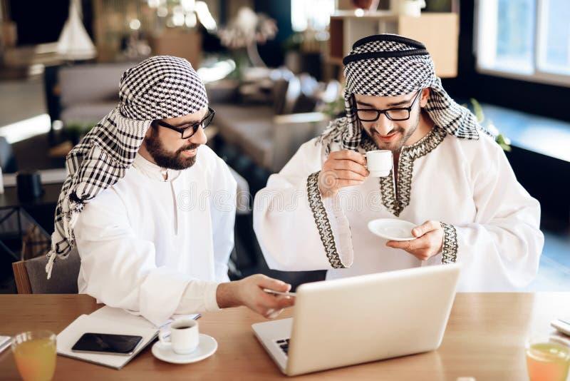 Deux hommes d'affaires arabes buvant du café à la table à la chambre d'hôtel images libres de droits