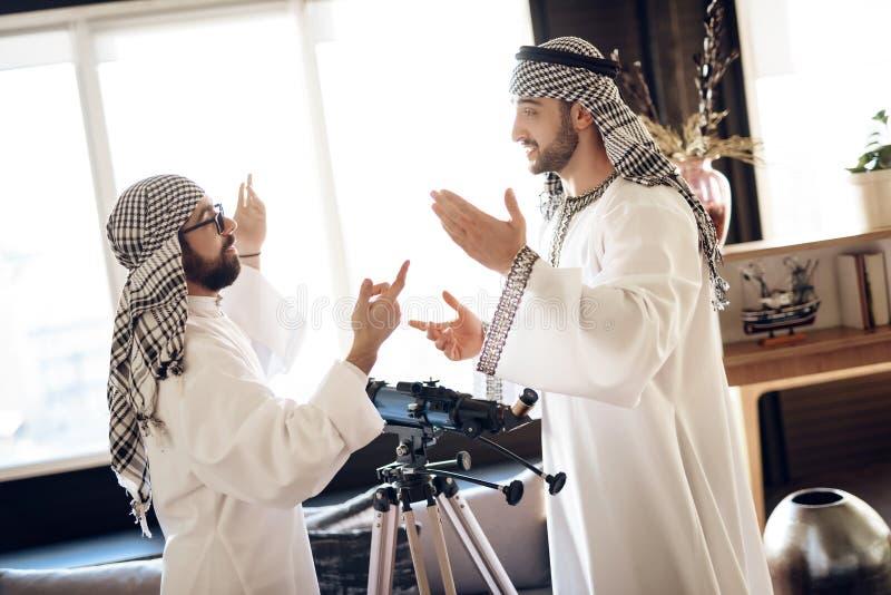 Deux hommes d'affaires arabes discutant derrière la fenêtre à la chambre d'hôtel photographie stock
