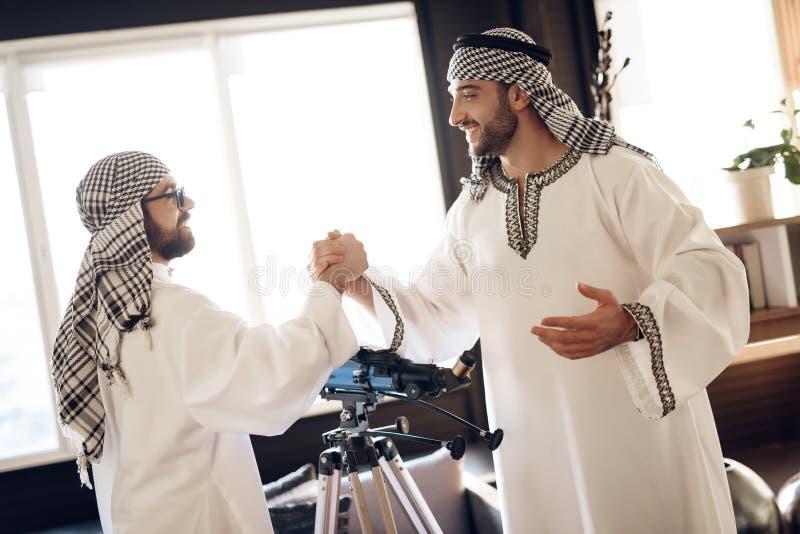 Deux hommes d'affaires arabes se serrent la main derrière la fenêtre à la chambre d'hôtel images libres de droits