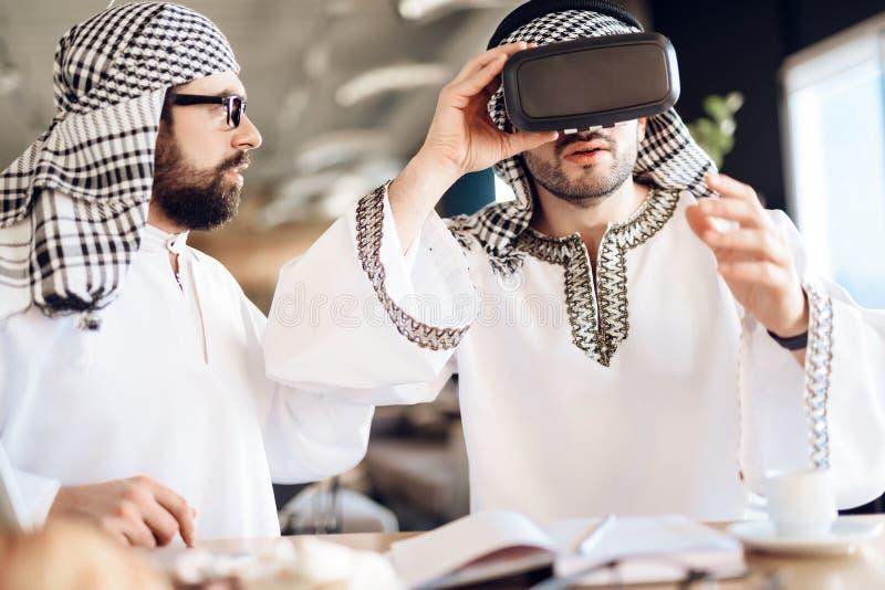 Deux hommes d'affaires arabes utilisant la réalité virtuelle à la table à la chambre d'hôtel image libre de droits
