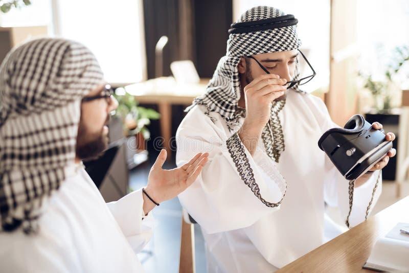Deux hommes d'affaires arabes utilisant le vr à la table à la chambre d'hôtel image libre de droits