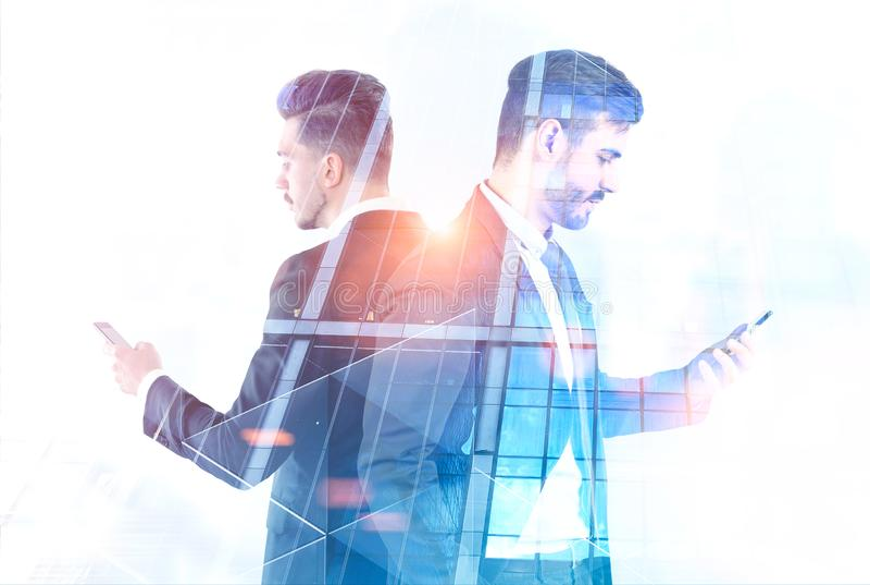 Deux hommes d'affaires avec des smartphones, gratte-ciel photo libre de droits
