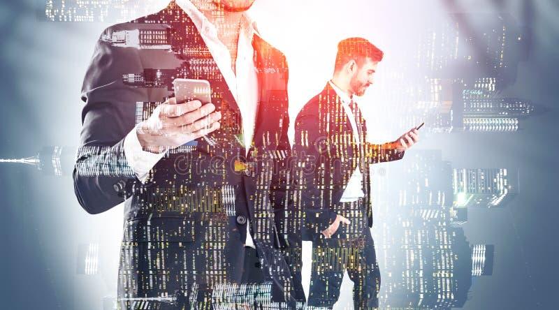 Deux hommes d'affaires avec des téléphones dans la ville de nuit photographie stock libre de droits