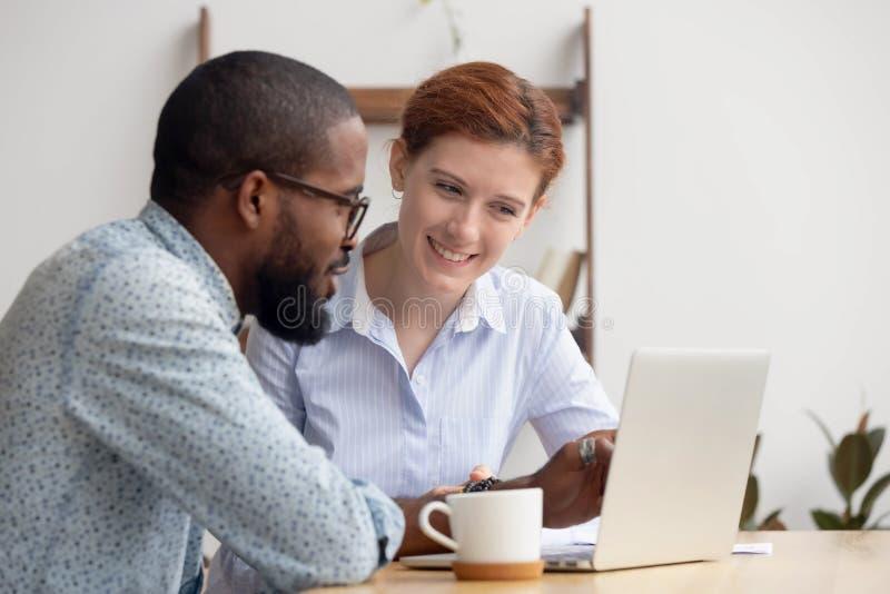 Deux hommes d'affaires de sourire divers discutant le projet en ligne photographie stock