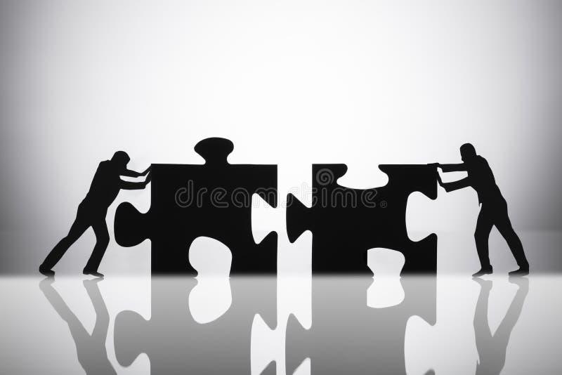 Deux hommes d'affaires joignant des morceaux de casse-t?te photos stock