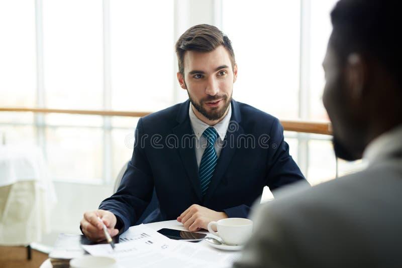 Deux hommes d'affaires négociant l'affaire en café photos stock