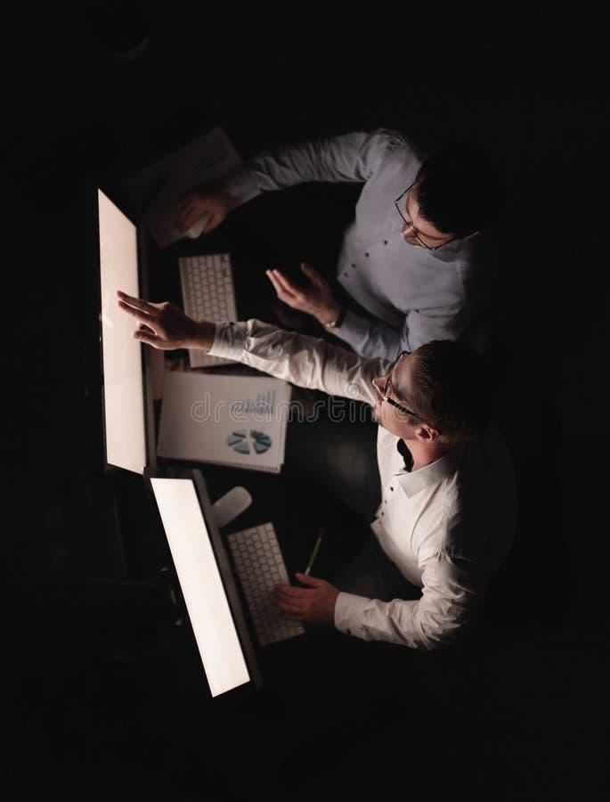 Deux hommes d'affaires rédigeant un rapport financier le soir photos stock