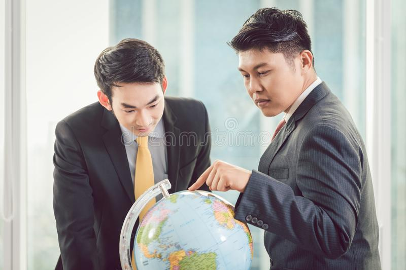 Deux hommes d'affaires regardant le globe photo stock