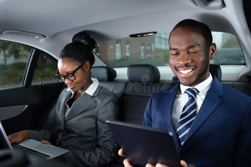 Deux hommes d'affaires s'asseyant ? l'int?rieur de la voiture utilisant des appareils ?lectroniques photos stock