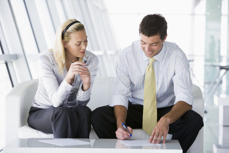Deux hommes d'affaires s'asseyant dans parler d'entrée de bureau image stock