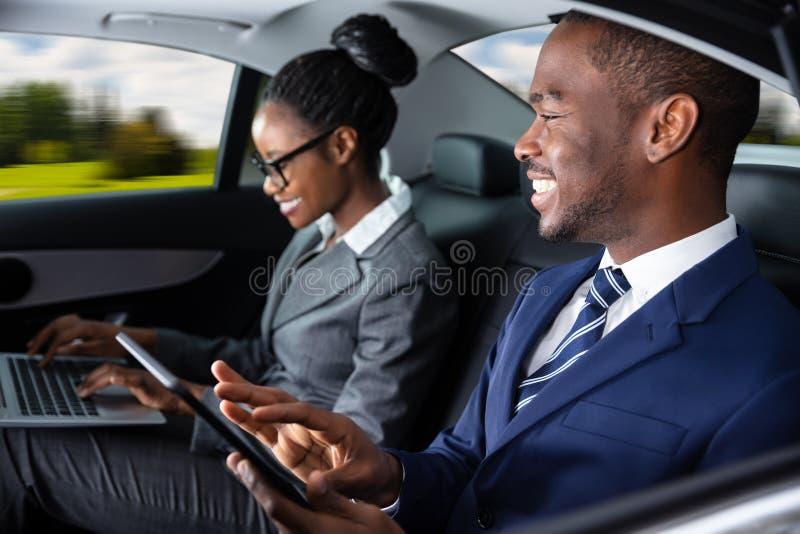 Deux hommes d'affaires s'asseyant ? l'int?rieur de la voiture utilisant des appareils ?lectroniques photo stock