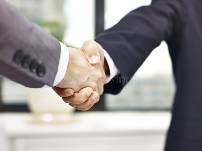 Deux hommes d'affaires se serrant la main photographie stock