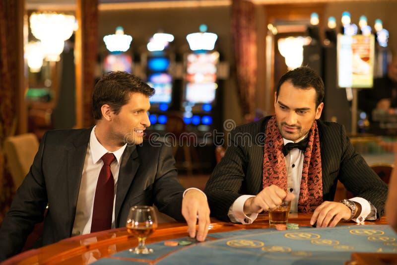Deux hommes dans les costumes derrière la table de jeu image libre de droits