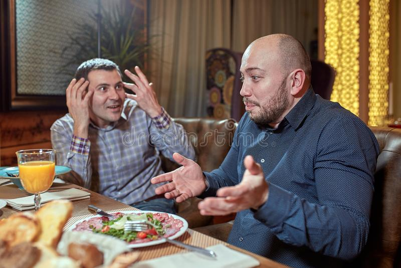 Deux hommes dans un restaurant discutant pendant le déjeuner photos stock