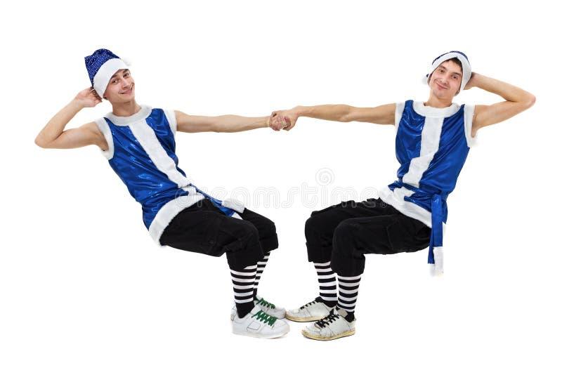 Deux hommes de Noël dans Santa bleue vêtx la danse contre le blanc d'isolement d'intégral photographie stock
