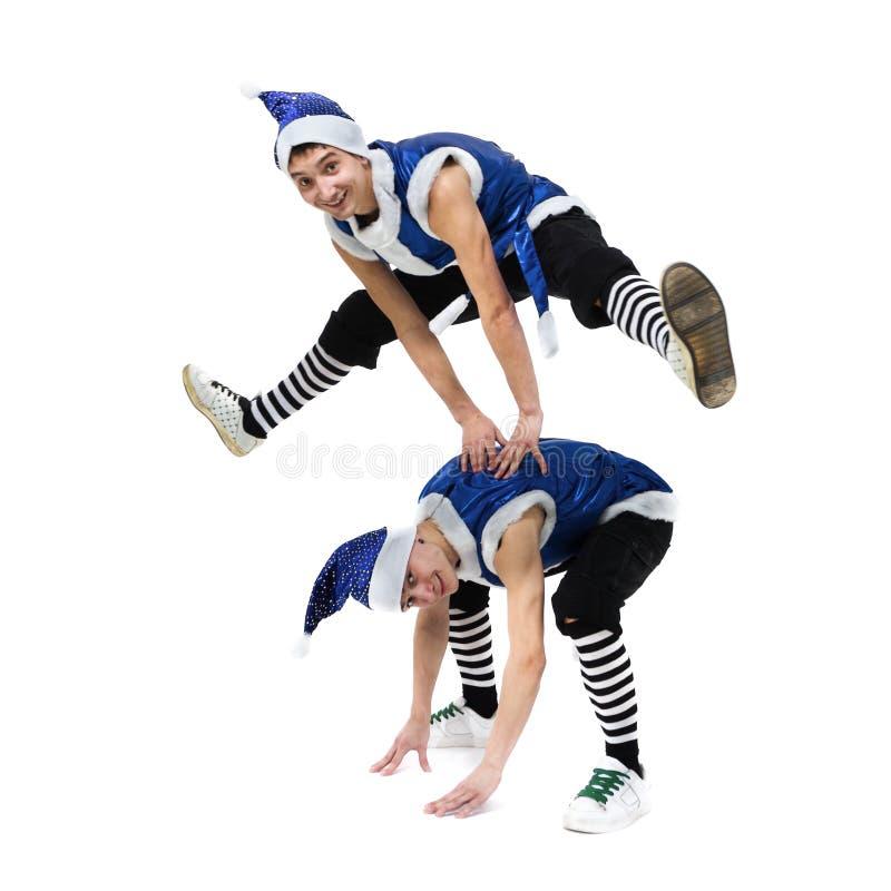 Deux hommes de Noël dans Santa bleue vêtx la danse contre le blanc d'isolement d'intégral photo stock