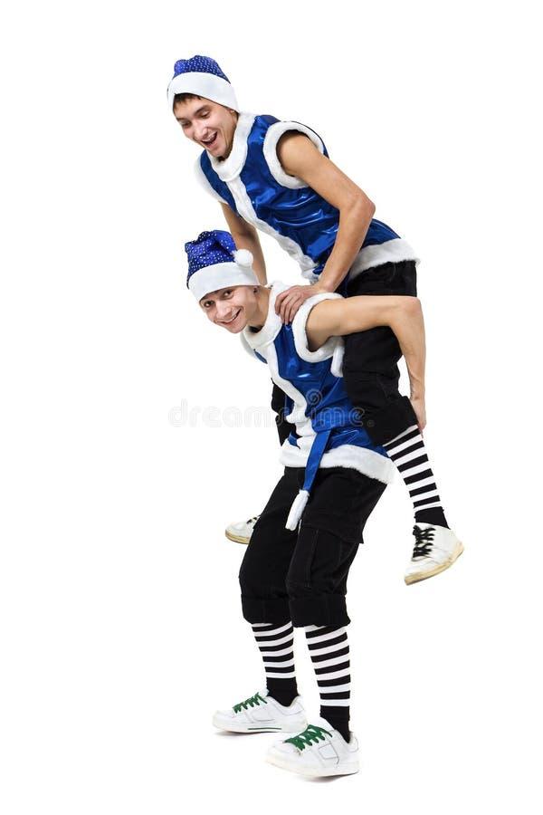 Deux hommes de Noël dans Santa bleue vêtx la danse contre le blanc d'isolement d'intégral photographie stock libre de droits