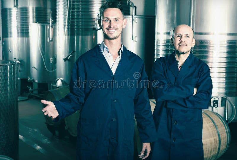 Deux hommes de sourire dans des uniformes se tenant dans des élém. de fermentation d'établissement vinicole photo libre de droits