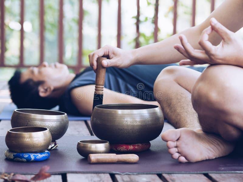 Deux hommes de yoga font le yoga extérieur avec des cuvettes de chant photos stock