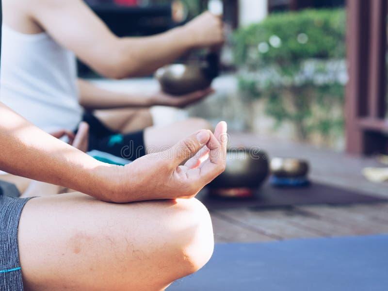 Deux hommes de yoga font le yoga extérieur avec des cuvettes de chant images stock