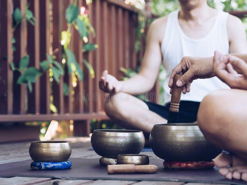 Deux hommes de yoga font le yoga extérieur avec des cuvettes de chant image libre de droits